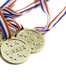 Three gold winner medals. Isolated against a white background Stock Images