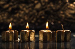 Three golden advent candles lit with bokeh background Royalty Free Stock Image