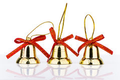 Three golden bell Christmas decorations with reflection Royalty Free Stock Photography