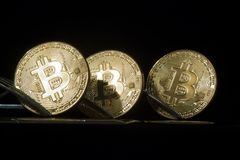 Three golden bitcoins with forks Stock Photography