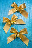 Three golden bows with little bells on old painted wooden board Royalty Free Stock Photos
