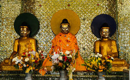 Three golden Buddha statue. Golden buddhas in Myanmar coating with gold and have gold tile at the background. The flower for praying and worship Stock Image