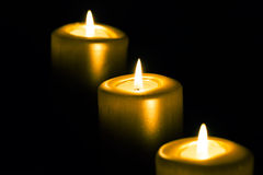 Three golden candles. On black background Stock Photos
