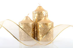 Three golden candles and bow Royalty Free Stock Photos