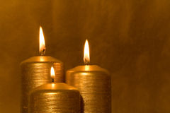 Three golden candles burning stock images