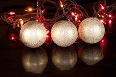 Three golden christmas balls are lying on a mirror flooring. Christmas holidays Royalty Free Stock Photo