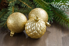 Three golden Christmas tree ball with fir branches Royalty Free Stock Photo