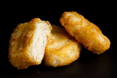 Three golden deep-fried battered chicken nuggets isolated on bla. Ck in perspective. One cut with meat showing Royalty Free Stock Photography