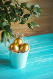 Three golden easter eggs on blue background Royalty Free Stock Photo