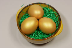 Three golden eggs in a bowl Royalty Free Stock Images