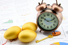Three golden eggs and a golden key with a clock on business and financial reports. Royalty Free Stock Image