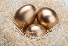 Three golden eggs in the  nest Royalty Free Stock Photography
