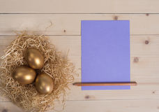 Three golden eggs in the nest and empty lilac card Royalty Free Stock Photos