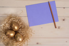 Three golden eggs in the nest and empty lilac card with pencil Royalty Free Stock Image