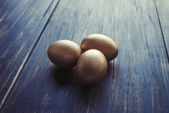 Three golden eggs Stock Images