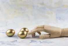 Three golden eggs touched by wooden puppet finger against painted clouds Stock Photo