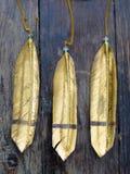 Three golden feathers Stock Photos