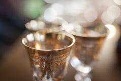Three golden glasses in the defocus. Close-up Stock Photo