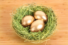 Three golden hen's eggs in the grassy nest Stock Photo
