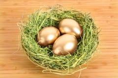 Three golden hen's eggs in the grassy nest Stock Photo