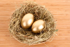 Three golden hen's eggs in the grassy nest Stock Images