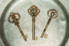 Three golden keys on iron plate Royalty Free Stock Photos