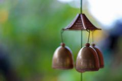 Three golden lucky bells hanging down from the celling by rope f stock image