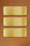 Three golden metal plates over wood texture background Royalty Free Stock Image