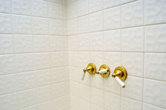 Three golden shower valve handles Royalty Free Stock Images