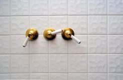 Three golden shower valve handles Stock Photography