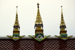 Three Golden Spires on a Temple Roof in Thailand. Three Golden Spires against a grey sky on the red tilled roof of the temple of Wat Chai Pra Kiat in Chiang Mai Royalty Free Stock Photos