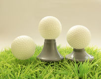 Three Golf ball on different supports , tee on grass Royalty Free Stock Images