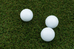 Three Golf ball. On the grass ground Stock Photos