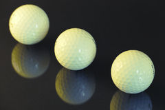 Three golf balls on a black background Stock Images