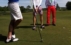 Three golf players on green field. Royalty Free Stock Image
