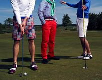 Three golf players on green field. Royalty Free Stock Photography