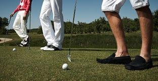 Three golf players on green field. Stock Photo