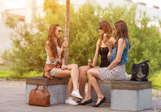 Three good girlfriends eat ice cream on a bench in the City Stock Images