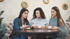 Three good young girlfriends met in a cafe. During this drink simultaneously cappuccino. Have long black hair. Slow video stock footage