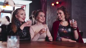 Three gorgeous women party hard with alcohol cocktails. Having fun with a true friends, drinking toast to friendship. Young and beautiful, happy memories stock footage