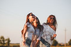 Three gorgeous young women in sunglasses dressed in the beautiful clothes are laughing outdoor on a sunny day. royalty free stock photography