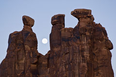 Three Gossips. A full moon sets behind the Three Gossips formation in Arches National Park Stock Image