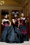 Three gothic girls with horns. Three gothic girls in black and red dresses with horns Stock Images