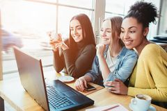 Three gourgeous best friends are in cafe. They are sitting vlose to a laptop which is on the table and loking to the royalty free stock photos