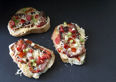 Three gourmet bruschetta made of bacon, tomatoes Royalty Free Stock Photography