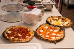 Three gourmet pizzas on a table. royalty free stock photography