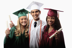 Three graduates in cap and gown. With diplomas Stock Photos