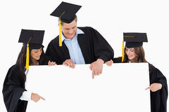 Three graduates pointing to the blank sign Royalty Free Stock Photo