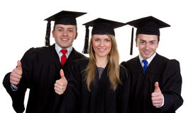 Three graduates with a thumbs up sign, isolated on white Royalty Free Stock Photo