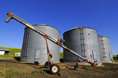 Three grain silos by the farmfield Royalty Free Stock Image
